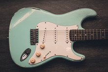 Light Blue Electric Guitar Against Brown Wood Background