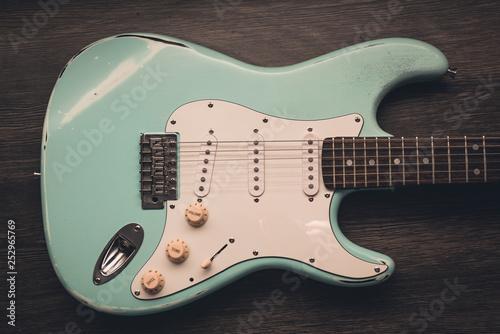 Fotomural Light blue electric guitar against brown wood background