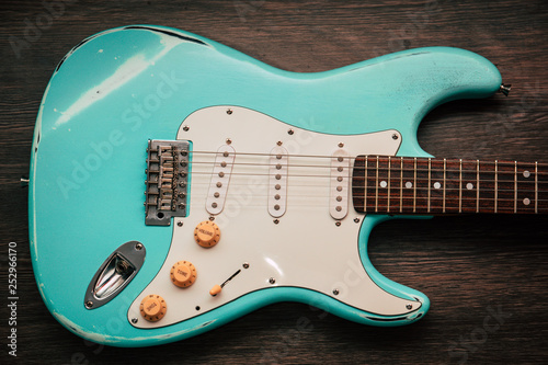 Light blue electric guitar against brown wood background Canvas Print