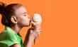 Leinwandbild Motiv Little baby girl kid kissing vanilla ice cream in waffles cone on yellow orange background in green t-shirt