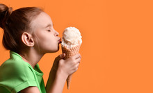 Little Baby Girl Kid Kissing Vanilla Ice Cream In Waffles Cone On Yellow Orange Background In Green T-shirt