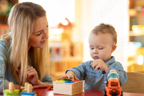 Fotografía  Kid playing logical toys with educator or mother in the classroom in nursery or