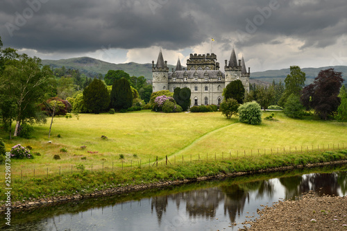 Inveraray Castle reflected in the River Aray at Loch Fyne with dark clouds and g Wallpaper Mural