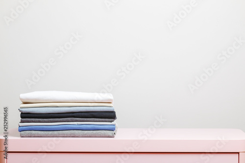 Fotografía  On a pink table is a stack of folded clothes