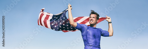 Fotografía  USA american athlete waving flag in success winning competition race on blue background panoramic banner
