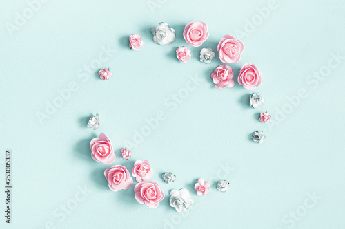 Flowers composition. Wreath made of rose flowers on pastel blue background. Flat lay, top view, copy space