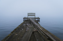 Empty Bench At The End Of An Old  Jetty, On A Foggy, Winter Morning.