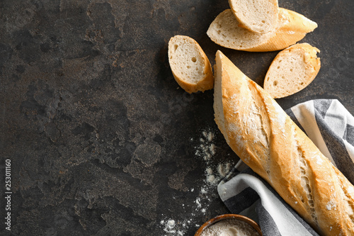 Cut French bread with flour on grey background Canvas Print