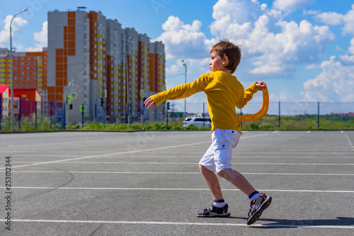 фотография the boy throws a boomerang into the blue sky
