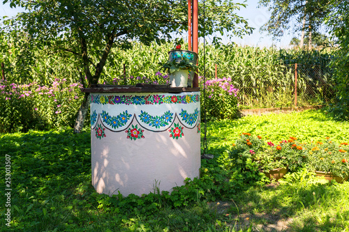 Fotografering  Painted old well decorated with a hand painted colorful floral motives, folk art