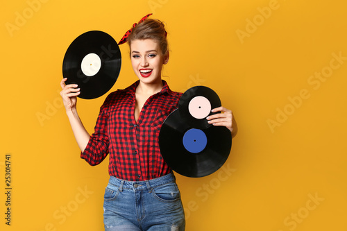 Beautiful pin-up woman with vinyl discs on color background Poster Mural XXL
