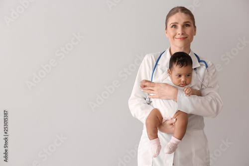Canvastavla  Pediatrician with African-American baby on light background