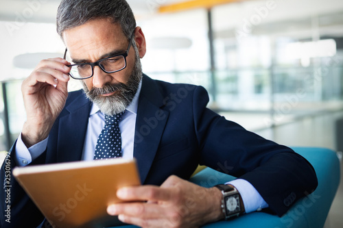 Business, technology and people concept - senior businessman with tablet pc working in office