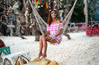 tanned young girl has a rest sitting in the hammock and looking to the side .on the background of the coastal camp