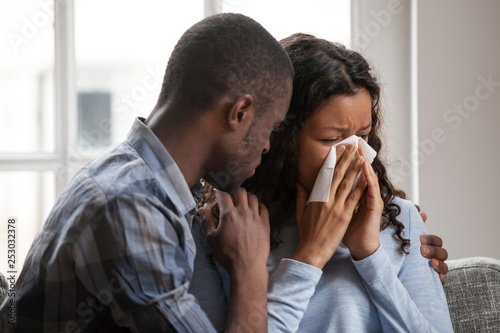 Fototapeta Caring black husband hug supporting sad crying wife