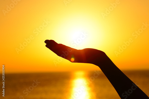 Fotografia  Woman hand holding sun at sunset on the beach