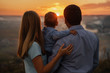 The young family happily feels playing with the child in the sunset.