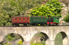 Model Of Locomotive Pushing Carriges On A Concrete Viaduct Bridge. Garden Model Train
