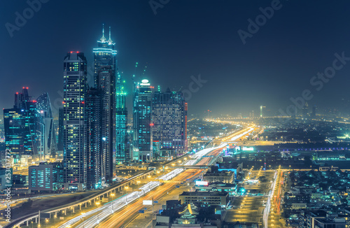 Colourful nightime skyline of Dubai, United Arab Emirates. Aerial view on highways and skyscrapers.