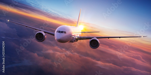 Poster Avion à Moteur Commercial airplane jetliner flying above dramatic clouds in beautiful sunset light. Travel concept.