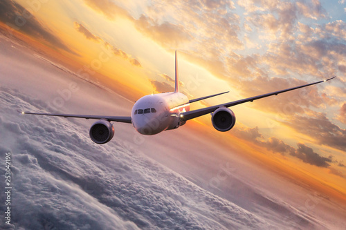 Türaufkleber Flugzeug Commercial airplane jetliner flying above dramatic clouds in beautiful sunset light. Travel concept.