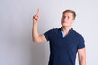 Leinwanddruck Bild - Portrait of young blonde handsome man thinking and pointing up