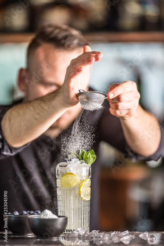 Cuadros en Lienzo  Professional barman making  alcoholic cocktail drink with fruits sugar and herbs