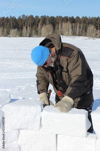 e866cfb78 Man in a blue hat and sunglasses building an igloo from snow blocks ...