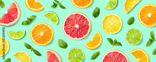 Colorful pattern of citrus fruit slices and mint leaves - 253054912