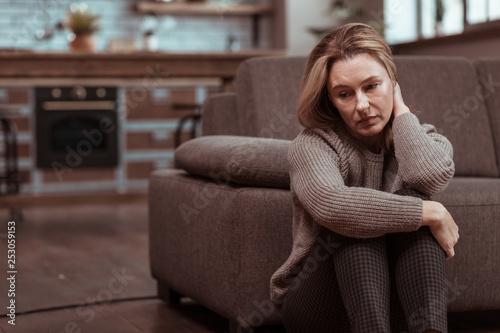 Obraz Woman wearing brown squared trousers feeling depressed - fototapety do salonu