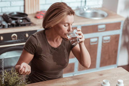 Fotografía  Blonde woman taking medicine after strong panic attack
