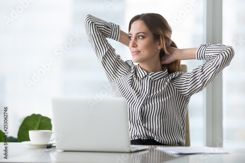 Fotografía  Happy businesswoman holding hands behind head finished resting at workplace