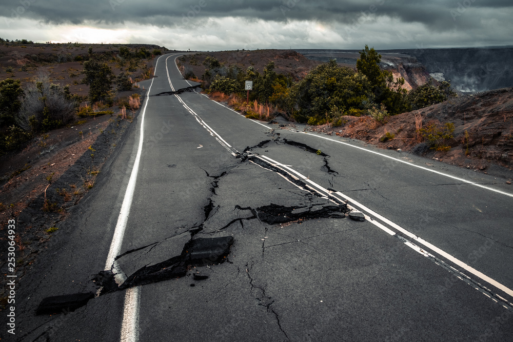 Fototapeta Damaged asphalt road (Crater Rim Drive) in the Hawaii Volcanoes National Park after earthquake and eruption of Kilauea (fume at upper right) volcano in May 2018. Big Island, Hawaii