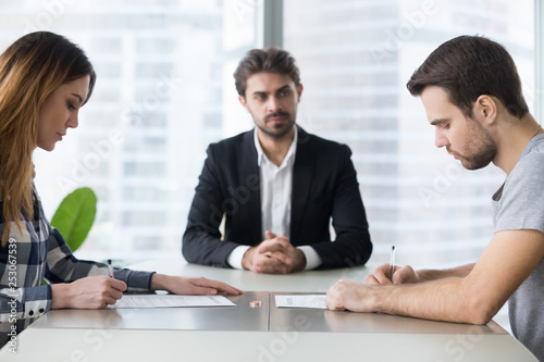 Spouses couple signing decree papers getting divorced in lawyers office