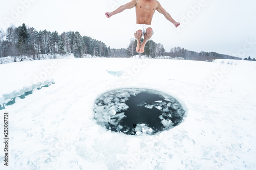 Fotografía  Young man jumps and flies into the ice hole made on the winter lake