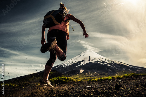 Pinturas sobre lienzo  Young woman, trail running athlete runs on the trail with loose ground and volca