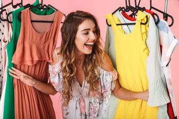 Photo of attractive woman in dress standing inside wardrobe rack full of clothes
