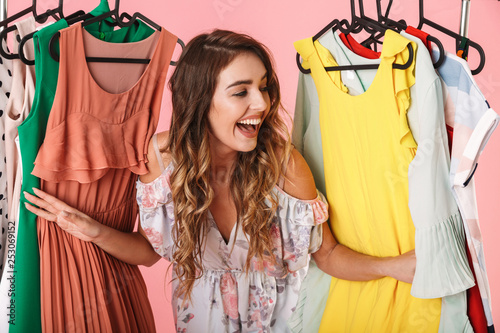 Vászonkép Photo of attractive woman in dress standing inside wardrobe rack full of clothes