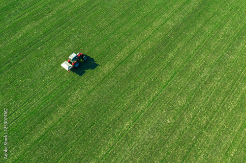 Wall Murals Green Agricultural tractor fertilizing wheat crop field with NPK