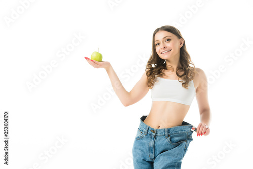Fotomural smiling slim young woman in big jeans holding green apple isolated on white