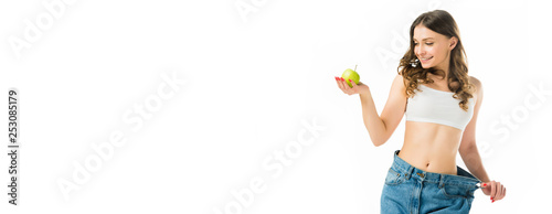 Fotomural smiling slim young woman in big jeans holding ripe green apple isolated on white
