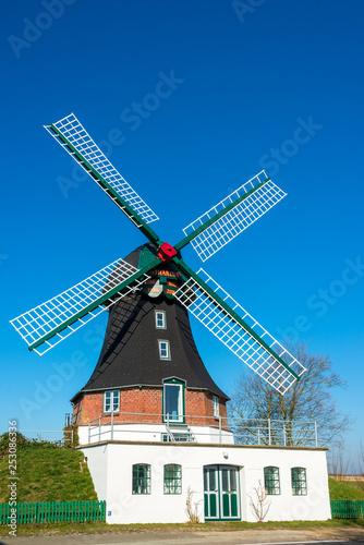 Fotografía  Windmühle in Oldeswort in Schleswig-Holstein vor blauem wolkenlosen Himmel