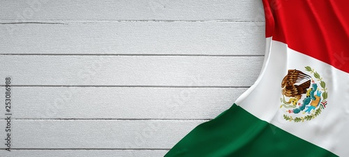 Mexican flag, on top of white wood. Wrinkled fabric.