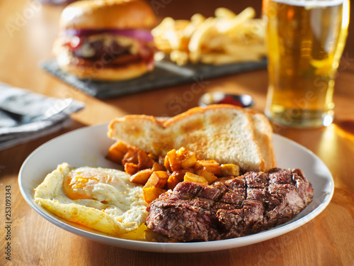 Fototapeta steak and eggs breakfast with toast and homestyle potatoes in restaurant obraz