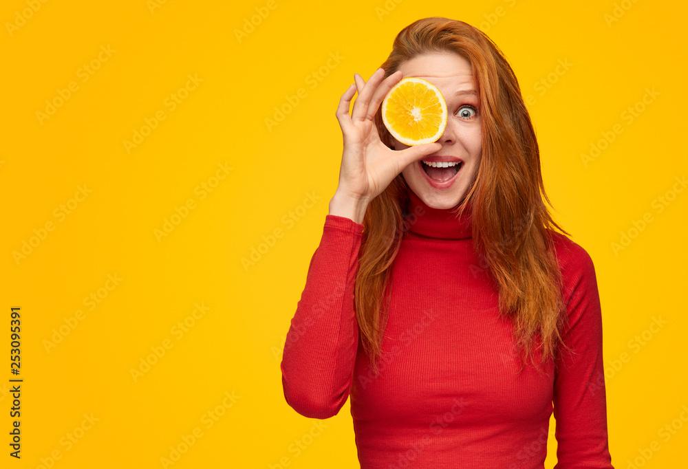 Fototapeta Expressive girl covering eye with orange slice