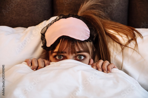 5cd47537575 Time to bed. Girl in sleep mask is looking at camera from under a ...