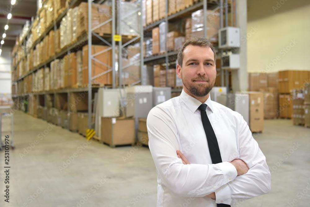 Fototapeta erfolgreicher Geschäftsmann im Anzug in einem Warenlager einer Spedition // successful businessman in a suit in a warehouse of a forwarding agency