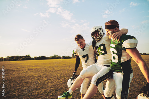 Fotografia  American football players carrying an injured teammate off the f
