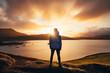 Leinwandbild Motiv Man standing in blue jacket looking at spectacular sunset over frostadavatn lake in Landmannalaugar in Iceland