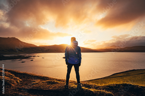 Obraz Man standing in blue jacket looking at spectacular sunset over frostadavatn lake in Landmannalaugar in Iceland - fototapety do salonu